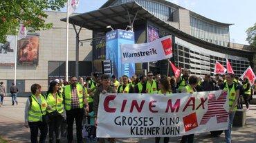 """Kundgebung in Hamburg vor dem CinemaxX-Verhandlungsauftakt: Die Demonstrant*innen tragen gelbe ver.di-Warnwesten und halten ein Plakat mit der Aufschrift """"CinemaxX Grosses Kino kleiner Lohn"""