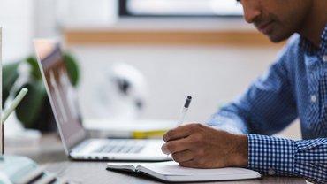 Ein Mann schreibt etwas in ein Notizbuch. Vor ihm auf dem Schreibtisch steht außerdem ein Notebook